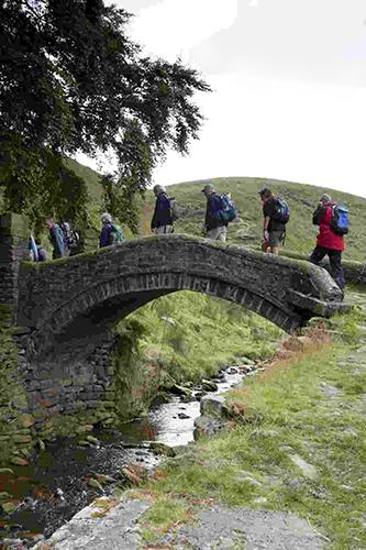 Walkers on packhorse bridge near Marsden Low Res
